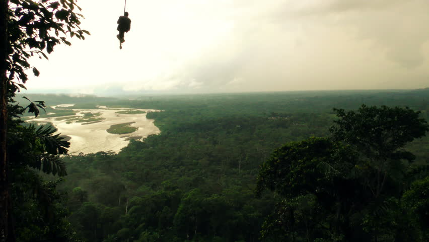 Slow motion shot of a man swinging over the Amazonian forest