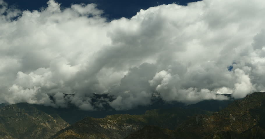4k time lapse of white puffy clouds mass rolling over Tibet mountaintop,clouds shadow running,roof of the World.gh2_08757_4k