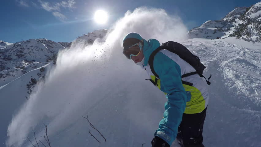 Snowboarder doing powder turns in fresh snow on the mountain
