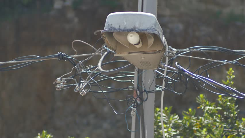 Close up view of a street lamppost. Complex maze of high voltage wires and terminals on pole