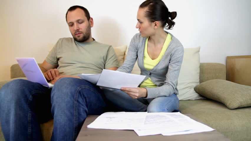 Couple sitting on sofa at home and calculating bills     - HD stock footage clip