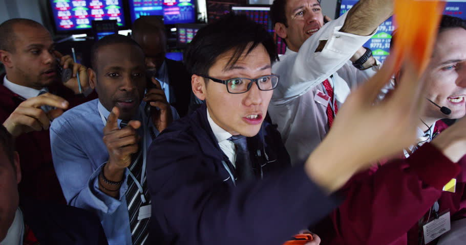 4K Diverse group of stockmarket traders frantically buying and selling on the trading floor