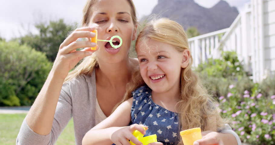 Mother and cute Daughter blowing bubbles in the yard happy family home RED DRAGON - 4K stock video clip