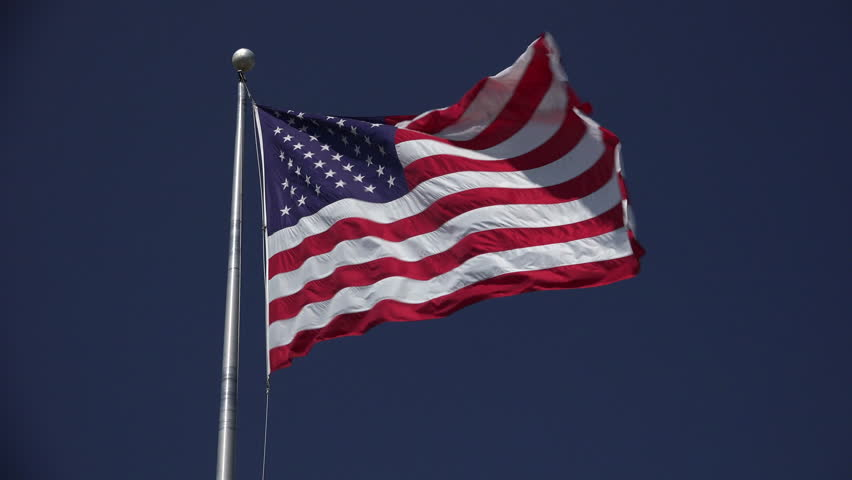 Looking up at high flying jumbo American flag waving in the breeze against a beautiful blue sky on a sunny day - 4K stock footage clip