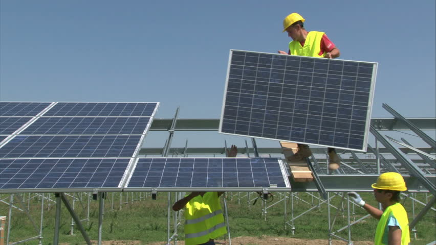 Workers are mounting panels on solar power-plant construction. - HD stock footage clip