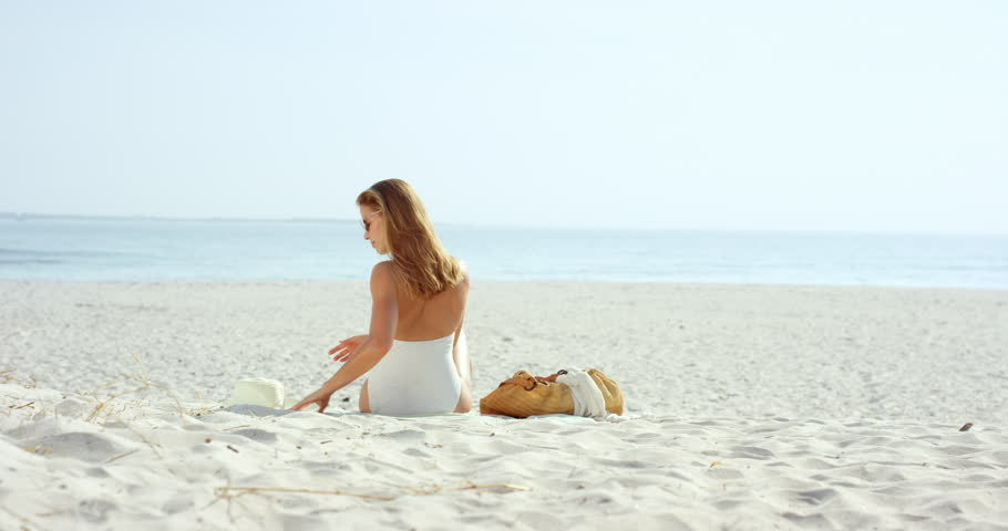 Attractive woman looking at view sitting on beach wearing one piece bathing suite
