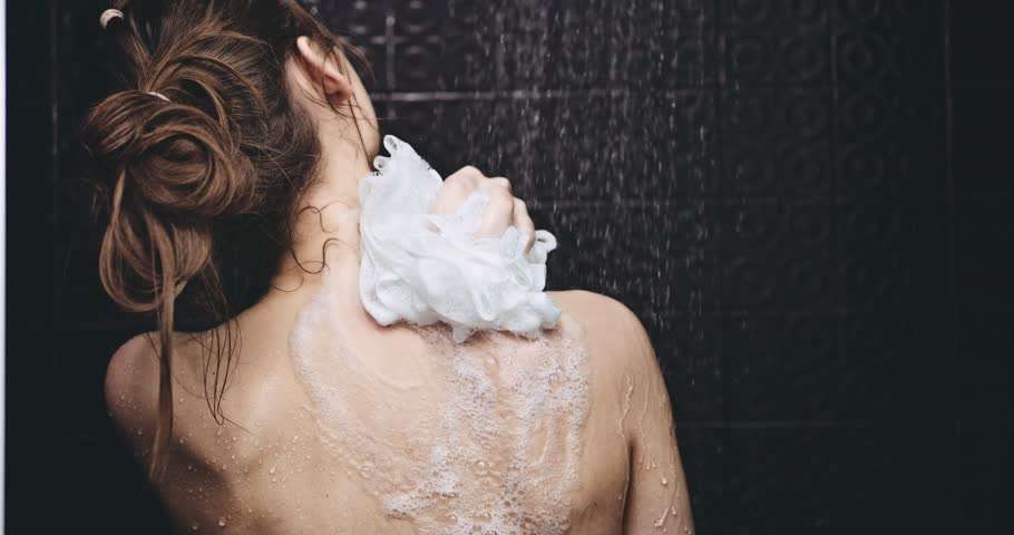 Woman taking shower in slow motion. Filmed in 4K DCi resolution. Young beautiful woman taking a shower and gently touching her skin, washing her back. Beauty and wellbeing concept.