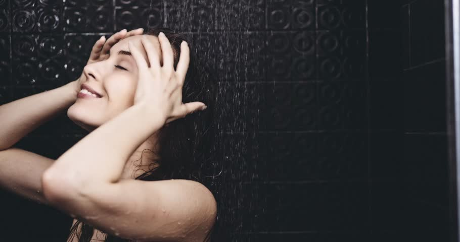 Woman taking shower in slow motion. Filmed in 4K DCi resolution. Young beautiful woman taking a shower and washing her hair, smiling. Beauty and wellbeing concept.