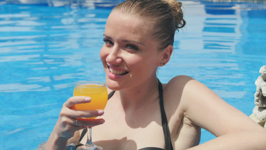 Young Pretty Woman Relaxing In Swimming Pool With Fresh Mango Juice And Fruits During Hot Summer