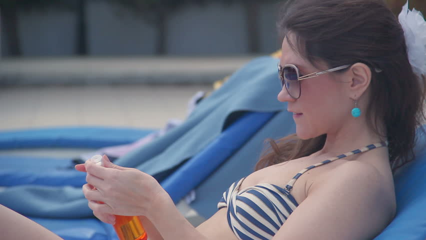 Pretty woman applying sunscreen to protect skin from ultraviolet