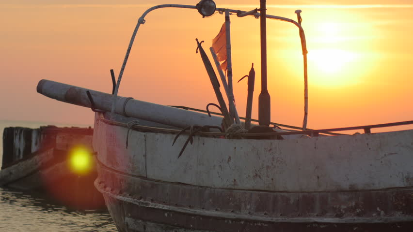 Old fishing boat moored to a pier during a summer sunset - 4K stock footage clip