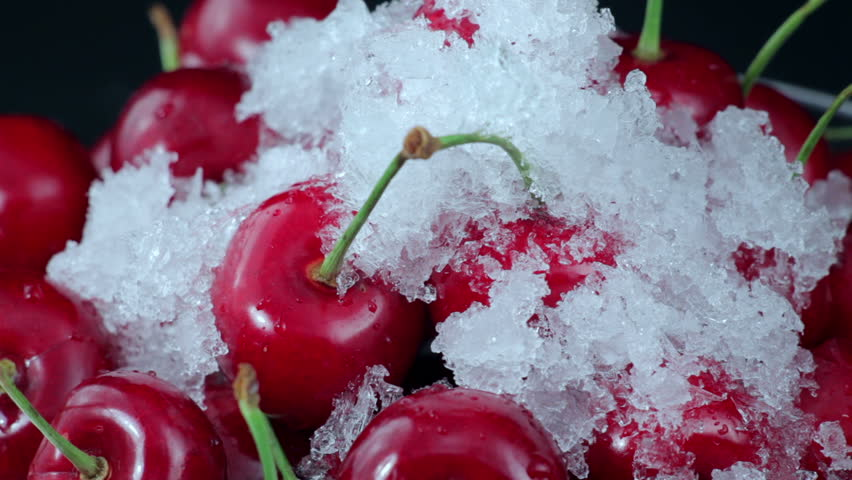A Group of Ripe Red Cherries in a Beautiful Plate With Melting Snow. Close up. Time Lapse