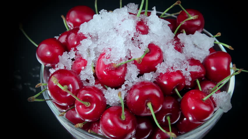 A Group of Ripe Red Cherries on The Plate Beautiful With Snow on The Rotating Table. Close up