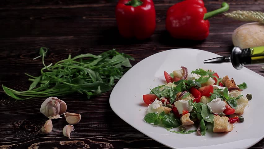 Bread salad with vegetables, herbs and mozzarella cheese. Chef pours salad with olive oil.