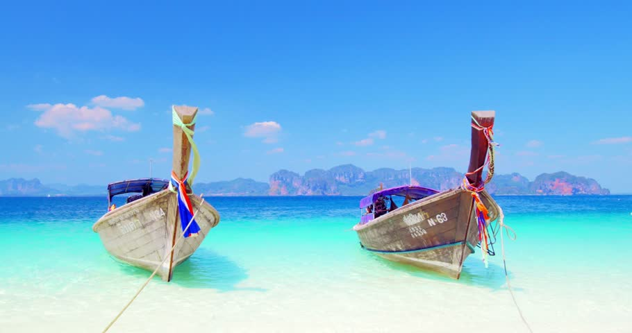 KRABI, THAILAND - 3 MAR 2015: Summer vacation travel background. Two wooden traditional thai boats on sea coast with sandy beach and calm clear water. Sunny day with blue sky and mountains in distance - 4K stock footage clip