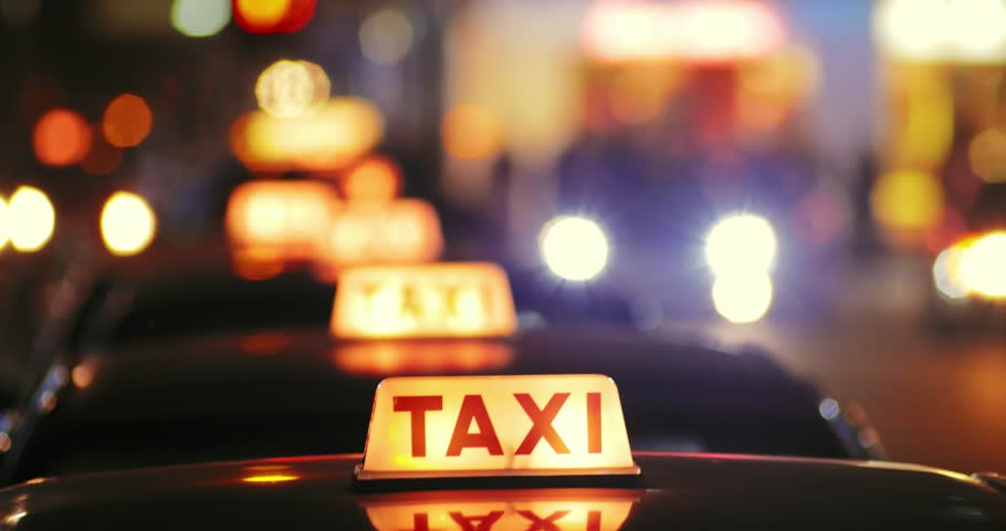 Blurred city background with row of taxis in Hong Kong downtown at night