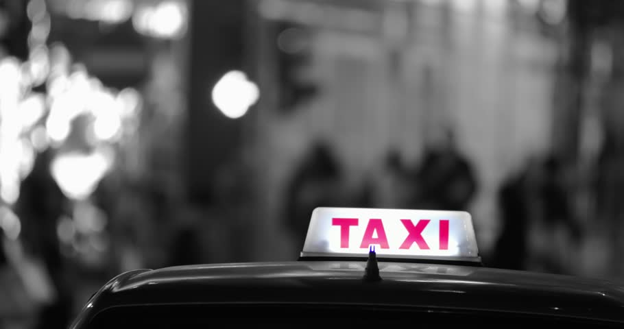 Cinematic style video of city street with people silhouettes moving on sidewalk taxi car with bright lit sign in front of camera