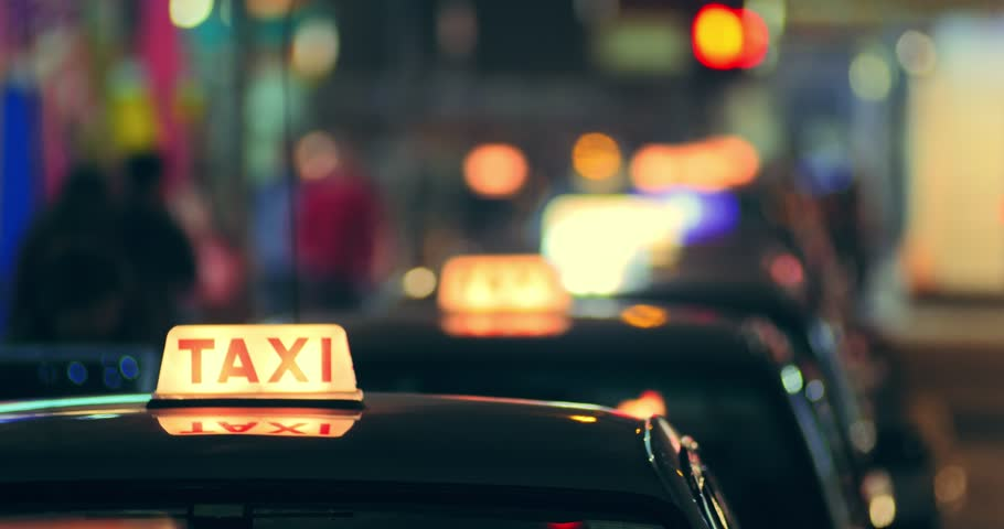 Many taxi cars in Hong Kong downtown at night. Abstract city background