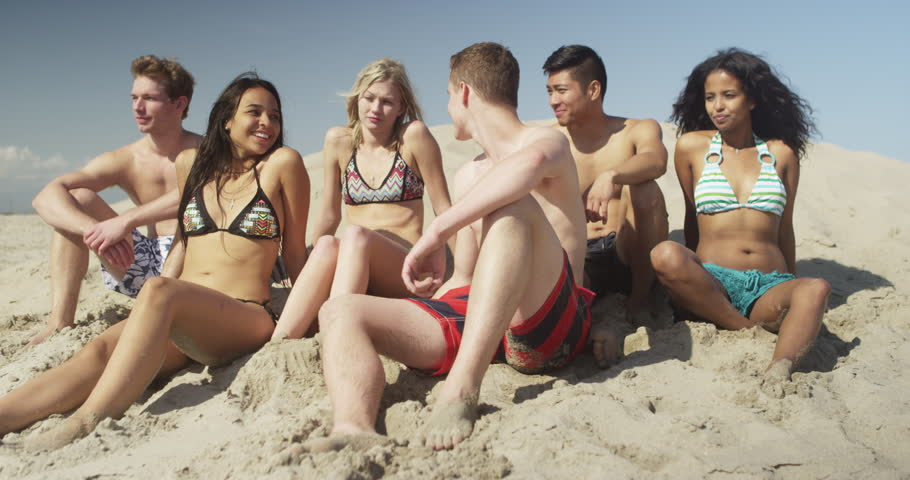 Young healthy group of multi ethnic friends sitting on the beach talking