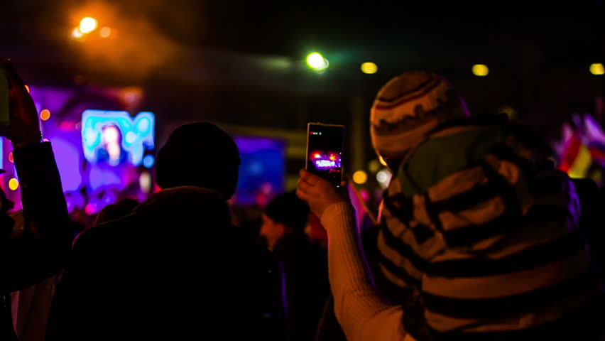Rear video shot of one woman with a child in warm clothes on her shoulders making a video record of a concert using her smartphone in a huge crowd of people. The background is multicolored and blurred