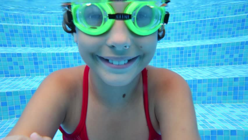 Happy girl in goggles swim underwater in pool. Close up - HD stock footage clip