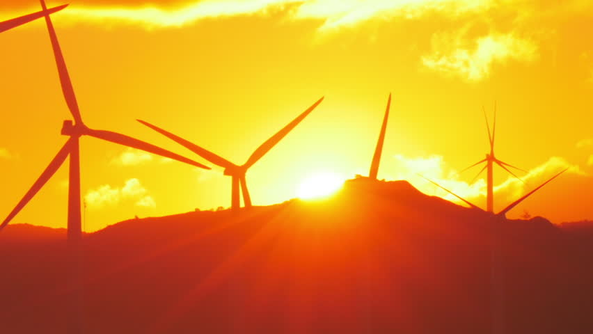 Rays of sun at sunset and rotating wind power generators - wind mill turbines - HD stock footage clip