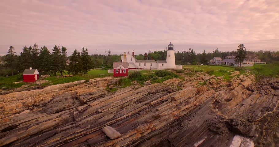 A wide to close-up aerial establishing shot of the Pemaquid Point Lighthouse in Maine at sunrise.