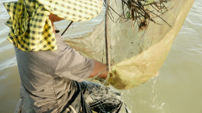 Upper close-up view on fisherman pulling drop net out of river and catching prawns  , southeast asia, cambodia