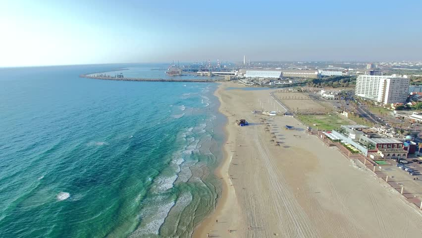 Aerial: Beautiful beach line with city on the background.