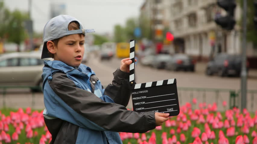 Boy claps clapperboard and goes out of frame