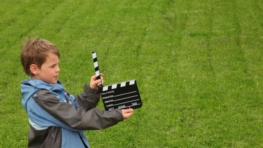 Boy claps clapperboard on field with green grass and walks out of frame