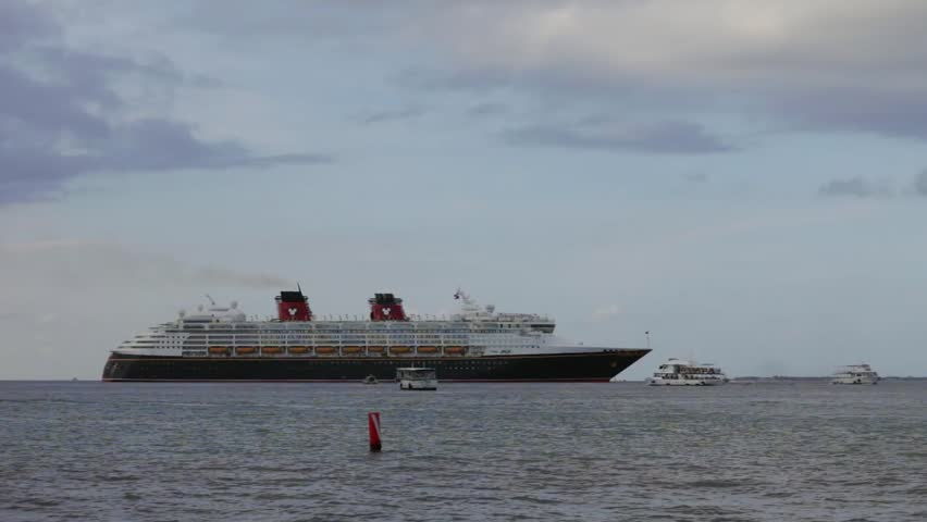 GRAND CAYMAN, CAYMAN ISLAND - 20 JULY 2012: tender boats are sailing aside of Disney large cruise ship