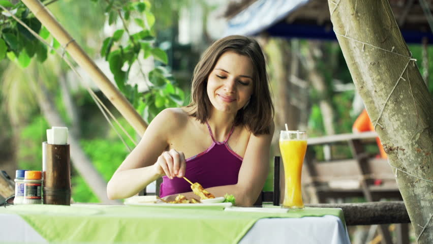 Young woman eating satay chicken sitting in exotic cafe