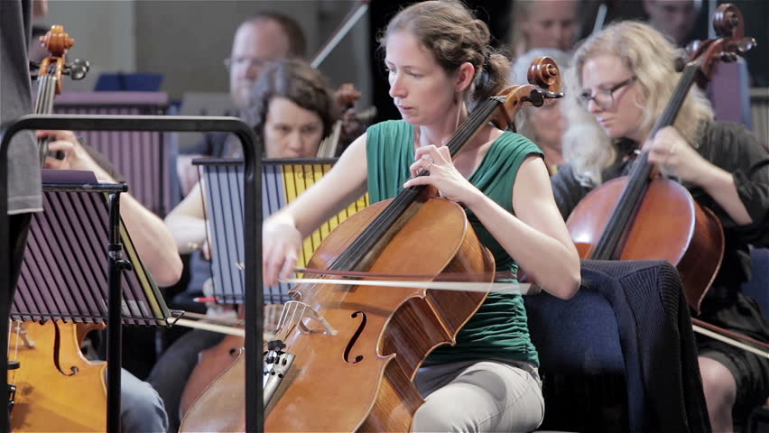 LONDON, UK - 8 JUNE 2013: Candid video footage with a pan over from the front desk cellos to the violins during a vigorous symphony orchestra rehearsal.