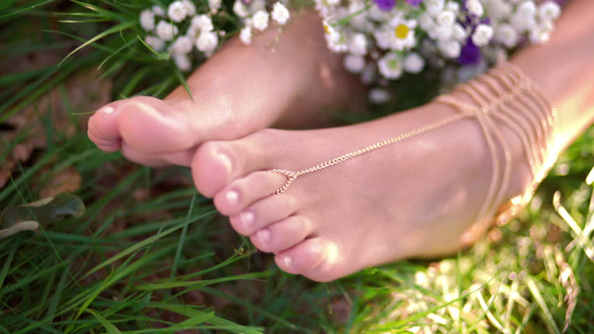 Cropped shot of a girl's hands resting on her ankles with her feet resting in lush green grass decorated with wild flowers and gold chain foot jewellery