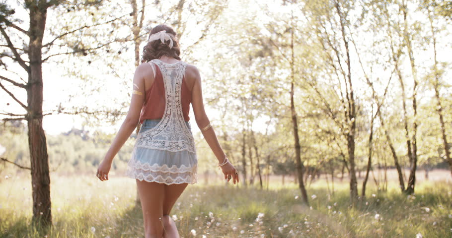 Rearview shot of a boho girl wearing a vintage lace top walking through a summer park with her arms out feeling free