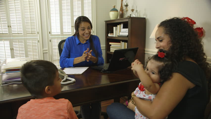 Cheerful CEO or small business owner meeting with a client and her children enjoys interaction with the cute baby girl. - HD stock video clip