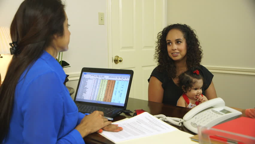 Pretty Latin American mother holding her cute little baby girl consulting with an accountant or financial advisor. - HD stock video clip