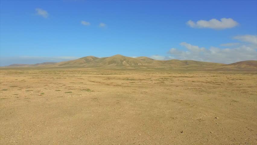 AERIAL: Flying over vast sandy desert towards the volcanoes on horizon in sunny summer