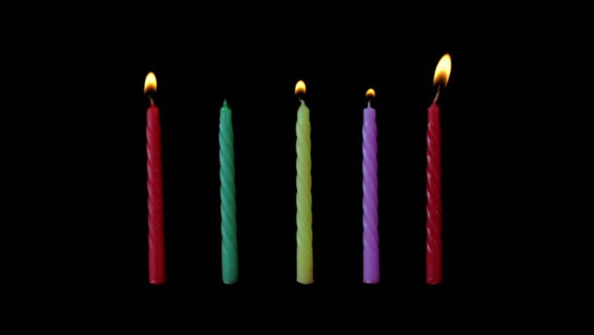 Burning five candles on black background