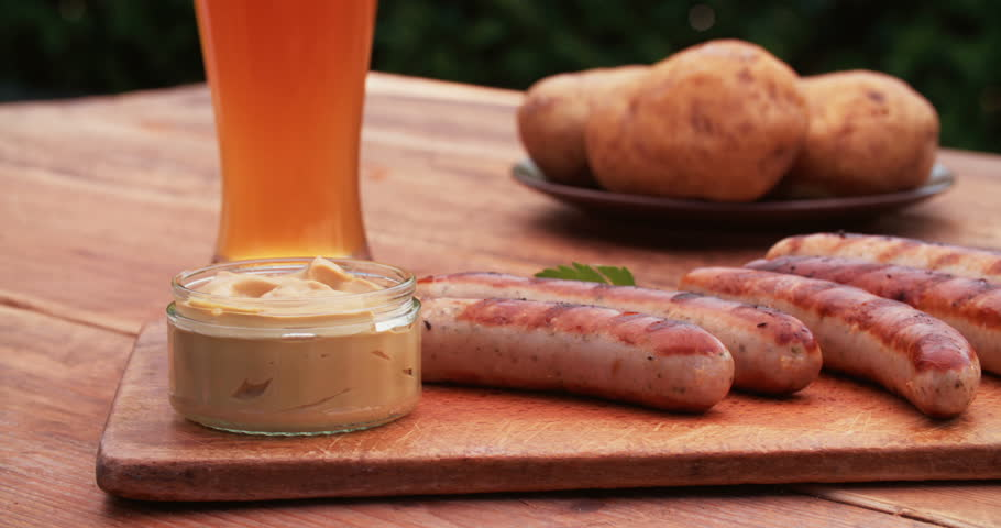 Delicious-looking grilled bratwurst sausages on a vintage wooden board accompanied by mustard and a tall glass of cold beer on a rustic wooden table outdoors - 4K stock footage clip