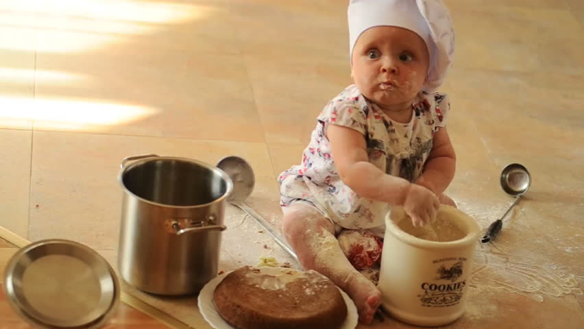 A little cute ten-months-baby-girl with cooking hoods on her head is sitting on the kitchen floor, she is heavily soiled with wheat flour - she's playing cook