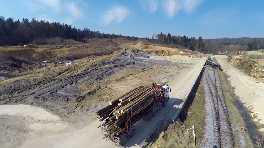 Truck full of log on is driving across the building side on a sunny day in the middle of a countryside, footage is taken with helicopter camera.
