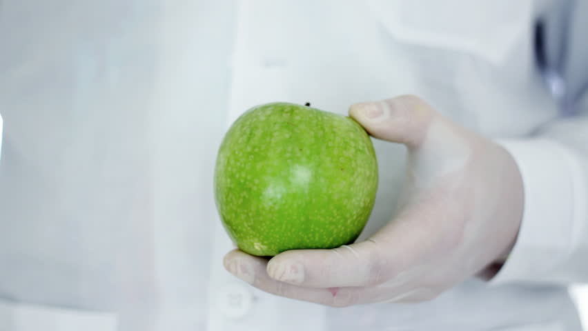 Male scientist hands with syringe injecting green apple