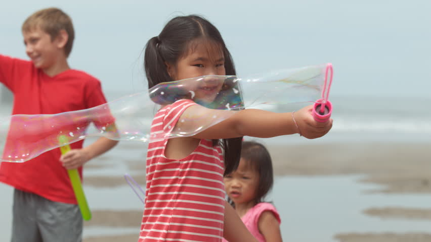 Children blowing bubbles at the beach slow motion