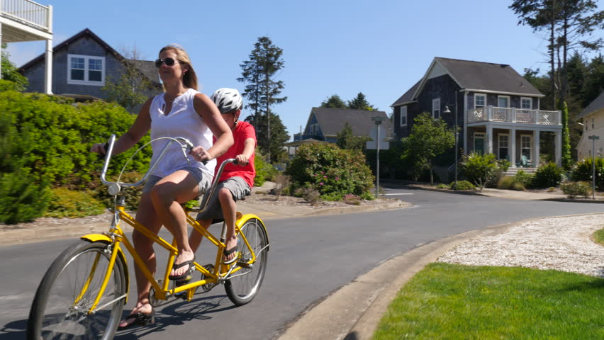 Mother and son riding tandem bicycle together in coastal vacation community