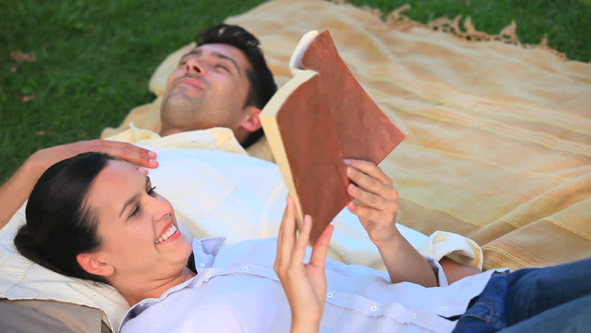 Woman reading a book in a park while her husband taking a nap - HD stock footage clip