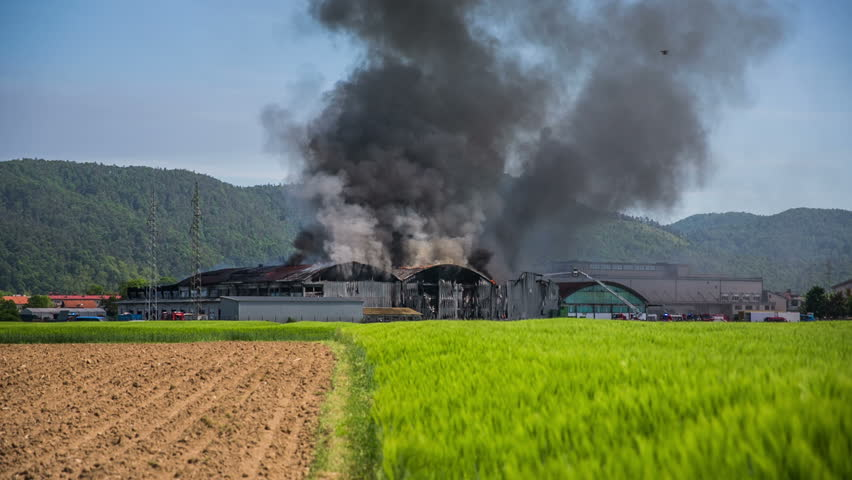 Building burning in the middle of nowhere. Wide shot of big field and a building in fire with a lot of smoke coming out. Sunny day with blue sky.