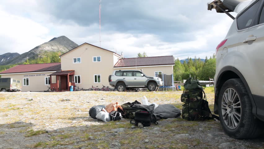 KHIBINS, RUSSIA - CIRCA JUN, 2015: Preparation to hiking with knapsacks is in mountains. Emercom or mountain rescue base and tourist camp are in the Khibiny Massif or Khibins in Russia