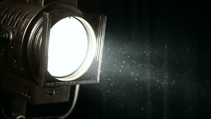 vintage theater spot light on black curtain with dust floating in front - HD stock footage clip